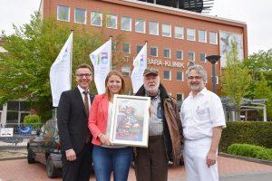 Das Jubiläumslogo weht bereits am Fahnenmast vor der St. Barbara-Klinik. Frank Lohmann, Lisa Kerkmann, Otmar Alt und Dr. Rainer Löb (v.l.n.r.) stellen das Jubiläumsprogramm vor.