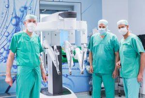 Prof. Dr. Jürgen Zieren, Direktor der Chirurgischen Klinik, Dr. Jens Peter Hölzen, Leitender Oberarzt, und der niederländische Experte für minimal-invasives Operieren und Robotik Prof. Dr. Ivo Broeders (v.l.n.r.) neben dem Da Vinci® Xi im OP.