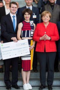 Preisverleihung: v. l. Titus Brinker, Gruppenleiterin der InitiativeAilís Haney aus Heidelberg und Bundeskanzlerin Angela Merkel.
